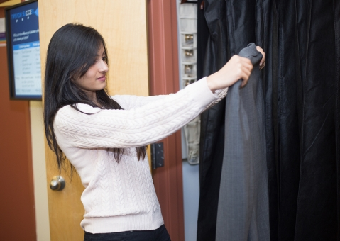 Student looks at suit in clothing closet