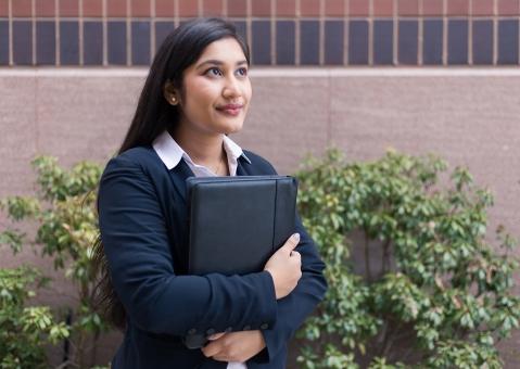 Student holding resume looking hopeful