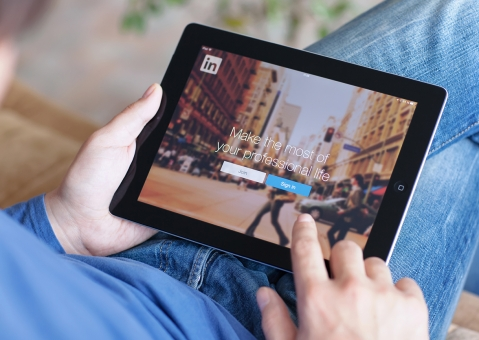 Man holding iPad with LinkedIn on screen